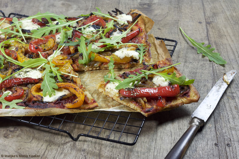 Speltpizza met ui, paprika, mozzarella en rucola